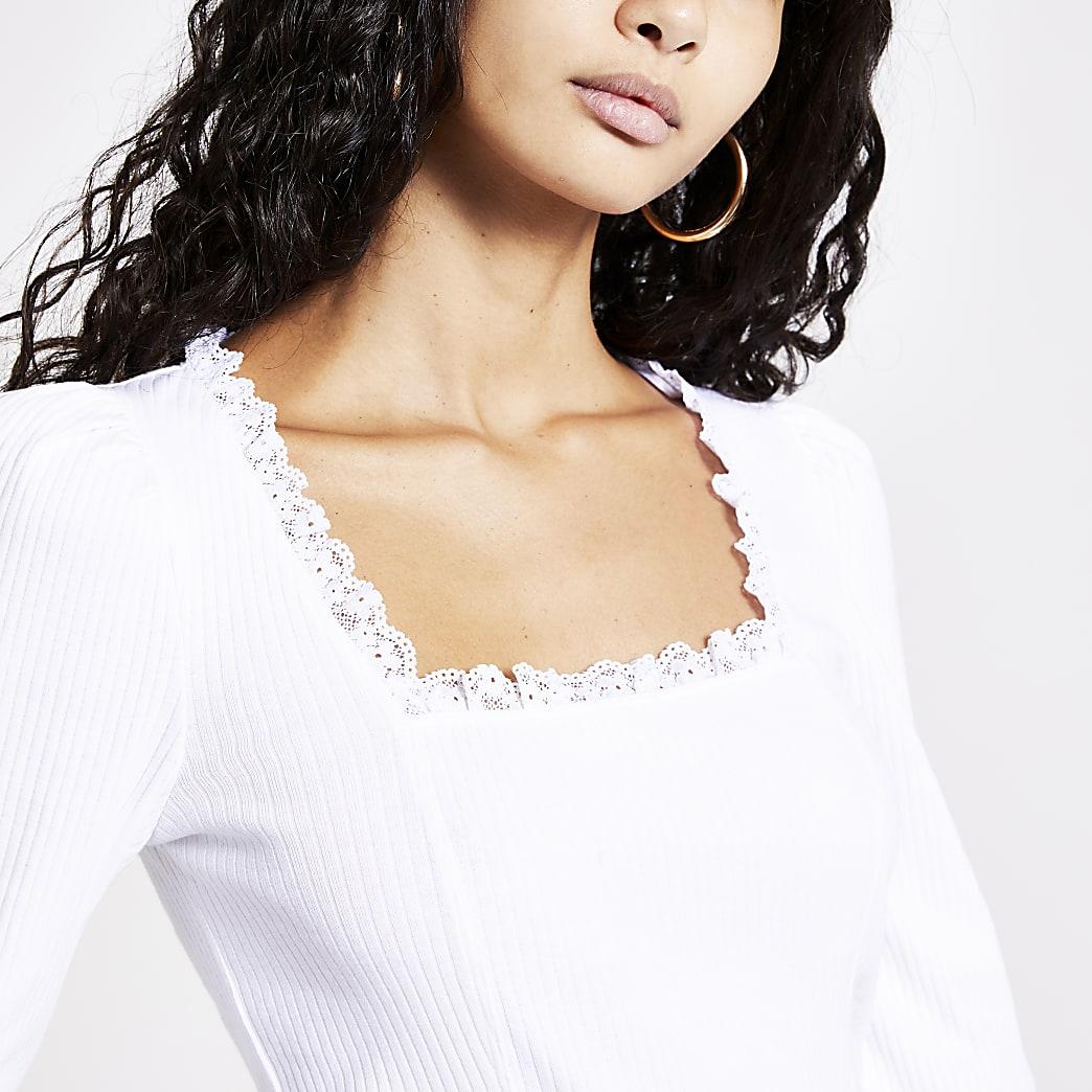 Witte top met lange mouwen en kant langs open hals