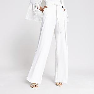 Witte broek met wijde pijpen, kwastjes en strikceintuur